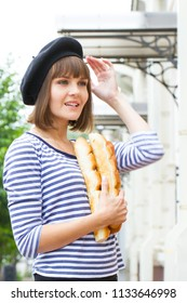 Young girl in beret and vest with loaves of white rolls
