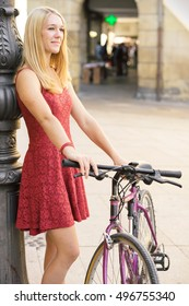 Young girl with bicycle leaning on a lamppost in the city