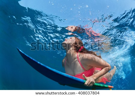 eb3818855a Young girl in bikini in action - surfer with surf board dive underwater  with fun under
