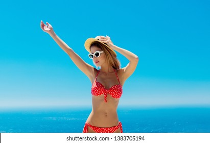 Young girl in bikini on terrace with blue sea and sky on background. Crete, Greece