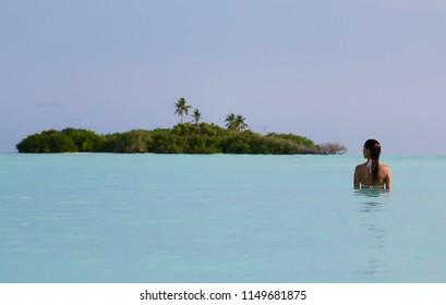 Young girl in bikini in the sea nearby the island, Maldives