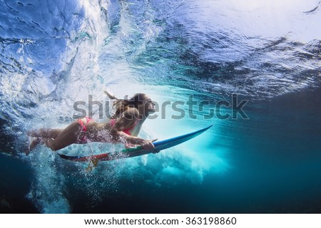 Young girl in bikini - surfer with surf board dive underwater with fun under big ocean wave. Family lifestyle, people water sport lessons and beach swimming activity on summer vacation with child