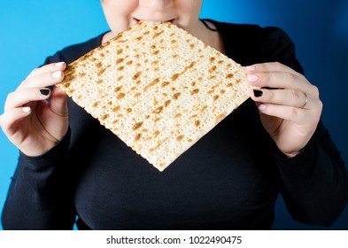 A young girl bites matzo. A family-friendly family holiday Pesach. Spring