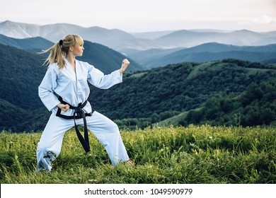 A young girl with a black belt coaches in martial art outdoors.