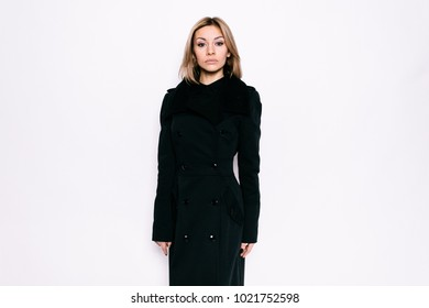 Young girl in a black coat on a white background