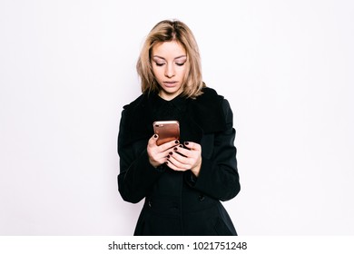 Young girl in a black coat talking on the phone on a white background