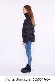 Young girl in a black down jacket and blue jeans isolated on a white background.