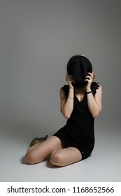 A young girl in a black dress covers her face with a hat. The beauty shy covers her face.