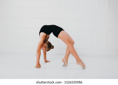 Young girl in a black dress doing gymnastics standing on one leg on white background