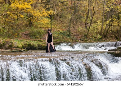 Young girl in a black dress posing on the edge of a waterfall
