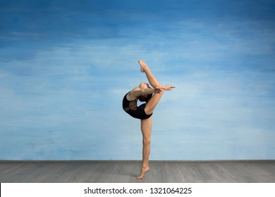 A young girl in a black gymnastic swimsuit gymnast makes an exercise standing backward and legs in semi splits on a blue background. A young girl gymnast performs kick back arms straightened back