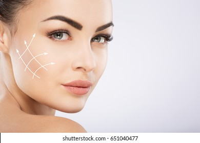Young girl with black hair fixed behind, big eyes, thick eyebrows and naked shoulders at gray background, copy space, beauty photo, close up, antiaging concept, lifting arrows on face.