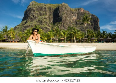 young girl with black hair in sunglasses and hat relaxing in the white boat in the ocean against the backdrop of palm trees and mountains. Mauritius