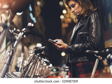 Young girl in black leather jacket using smartphone on background illumination glow bokeh light in night atmospheric christmas city, hipster biking going to work by bicycle on urban street, ecology
