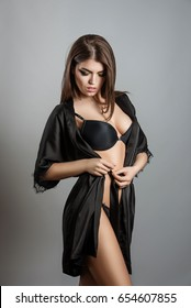 young girl in black lingerie and black satin robe on a light background
