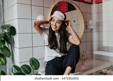 Young girl in black pajama pants and sleep mask poses in bathroom