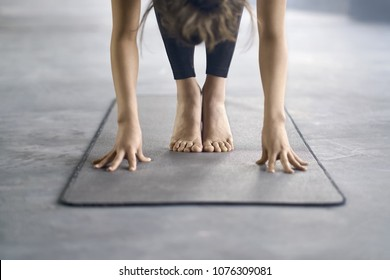 Young girl in black pants engaged in yoga in the gym. She stands on the mat and does a forward tilt and holds hands on the floor. Closeup. Horizontal.