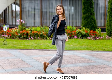 A young girl with a black T-shirt and gray trousers is photographed on the street. Beautiful woman on a walk in the park. Hipster girl posing in the city