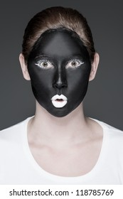 a young girl with black and white makeup