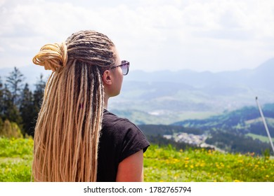 Young girl with blond dreadlocks looks at a beautiful mountain range.