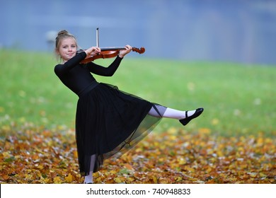 A young girl with blond hair is playing violin with fun.