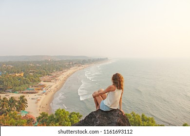A young girl with blond hair sits on top of a mountain and looks at the sea and beach of the village of Arambol, Goa, India. The beach from a height. Relax and relax alone with nature.
