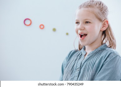 Young girl with blonde hair enjoying being at a speech therapy class