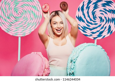 Young girl with  blonde hair wearing top and pink cap standing with huge sweet lollypops at pink studio background, candy lover, posing with donuts, funny.