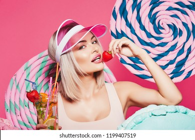 Young girl with blonde hair wearing top and pink cap standing with huge sweet lollypops at pink background, candy lover, drinking lemonade, close up, sweets lover.