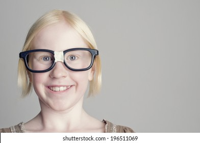 A young girl with blonde hair wearing glasses and smiling.