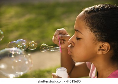 Young girl blowing bubbles outside. Horizontally framed shot.