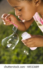 Young girl blowing bubbles outside. Vertically framed shot.