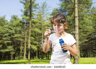 Young girl blowing bubbles in park. Copy space