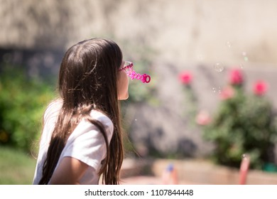 A young girl is blowing homemade bubbles, outside, during summer break.