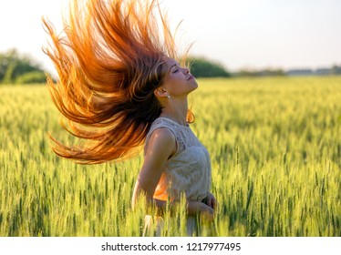 Young girl with blowing red hair in a field at sunset