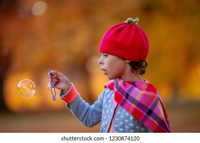 young girl blowing soap bubbles in the park
