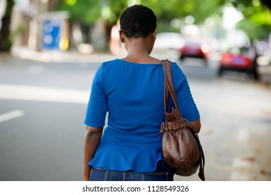 young girl in blue camisole with handbag walking while giving back to the camera.