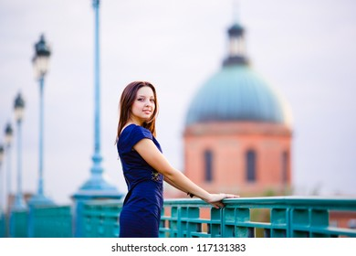 Young girl in a blue dress on La Grave hospital background in Toulouse, France