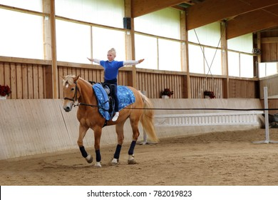 young girl with blue dress is vaulting
