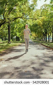 Young girl with blue eyes joging in the park. Autumn weather, yellow foliage.