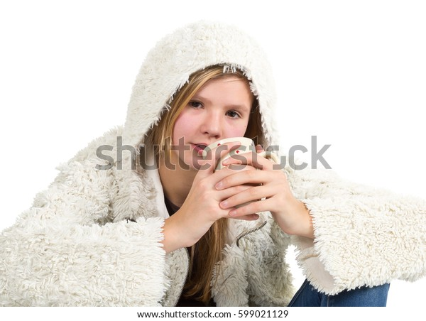 Young girl with blue jeans and winter jacket sitting, holding cup  isolated on white background
