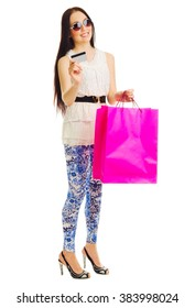Young girl in blue pants with bags and credit card isolated