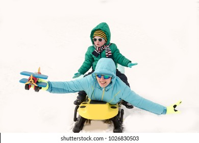 Young girl in a blue ski suit plays in the snow with her children. Yellow sledges, sunglasses, bright clothes. Children are happy together. The concept of a funny winter vacation for the whole family