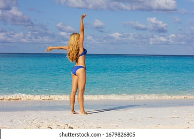 Young girl in a blue swimsuit on the beach. The blonde with long hair takes a sun bath. Girl with a beautiful figure on the beach. Woman athlete with hands up.