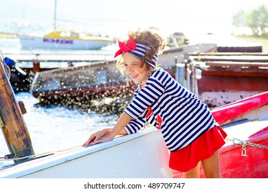 young girl with the boat, looking around and smiling