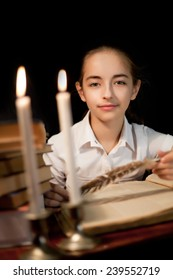 Young girl with book and candles at night library
