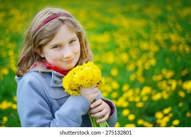 Young girl with bouquet of yellow flowers on meadow full of dandelions. MANY OTHER PHOTOS FROM THIS SERIES IN MY PORTFOLIO.
