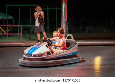 Young girl and boy driving a bumper car at a amusement park at night.