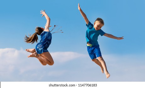 YOUNG GIRL AND BOY JUMPING AS FLYING AGAINST THE BLUE SKY, HAPPY ACTIVE KIDS ENJOYING LIFE AND FREEDOM