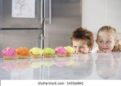 Young girl and boy peeking over counter at row of cupcakes